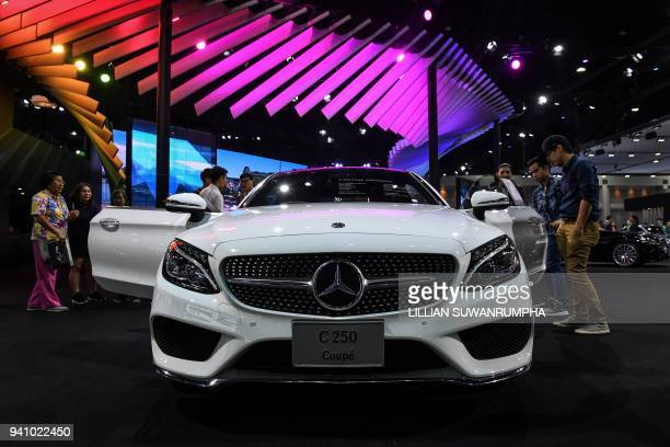 People gather around a Mercedes-Benz C250 Coupe during the annual Bangkok International Motorshow in Bangkok on April 2, 2018. / AFP PHOTO / LILLIAN...