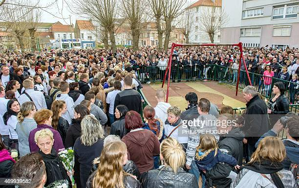 People gather around a playground during a march on April 16 2015 in Calais northern France in homage to a nineyearold girl who was killed a day...