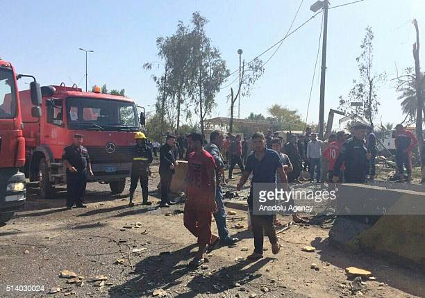 People gather around a scene after a suicide attack was carried out with a bomb laden vehicle on the al Asr checkpoint at the entrance of Babil Iraq...