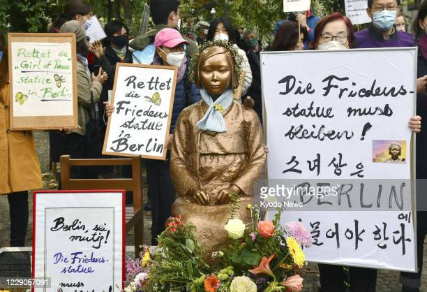 """People gather around a statue symbolizing Korean """"comfort women"""" forced to work in Japanese wartime military brothels in central Berlin on Oct. 13 in..."""