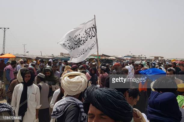 People gather around a Taliban flag as they wait for relatives released from jail in Afghanistan following an 'amnesty' by the Taliban, near the...
