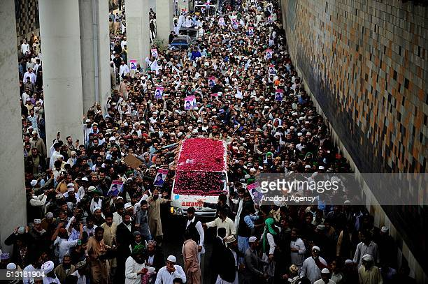 People gather around an ambulance which carries the body of Mumtaz Qadri former police bodyguard who shot dead Punjab's governor Salman Taseer in...