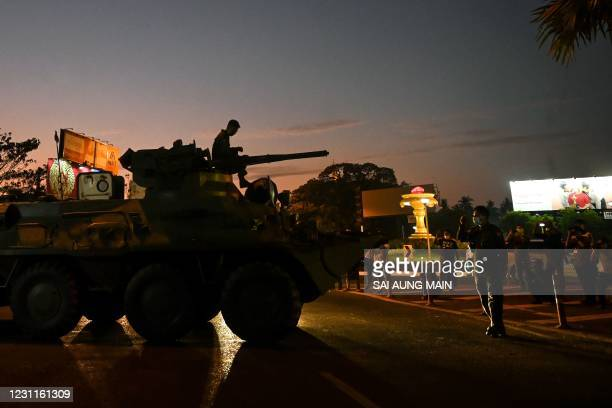 People gather around an armoured vehicle maneuvering on a city street, following days of mass protests against the military coup, in Yangon on...