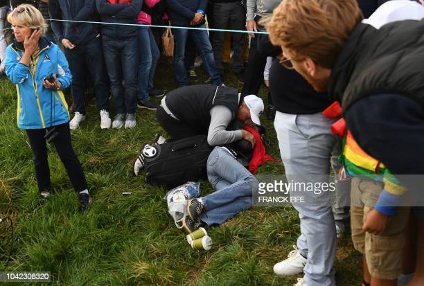 TOPSHOT People gather around an injured spectator during a fourball match on the first day of the 42nd Ryder Cup at Le Golf National Course at...