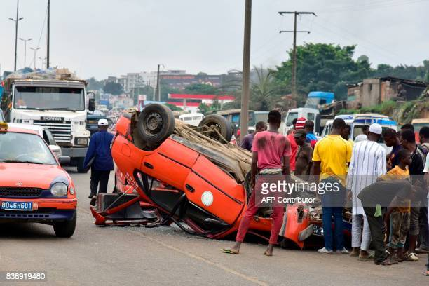 People gather around an overtuned and damaged taxi in Abidjan on August 25 after a collision between two taxis / AFP PHOTO / ISSOUF SANOGO