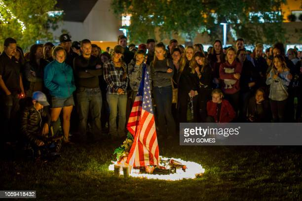 TOPSHOT People gather around candles and a US flag during a vigil to pay tribute to the victims of a shooting in Thousand Oaks California on November...