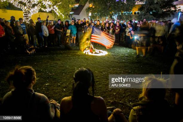 People gather around candles and a US flag during a vigil to pay tribute to the victims of a shooting in Thousand Oaks, California, on November 8,...