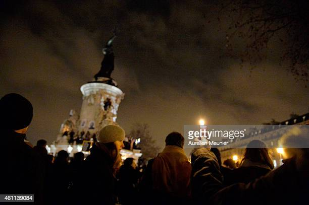 People gather around candles and pens at the Place de la Republique in support of the victims after the terrorist attack earlier today on January 7...