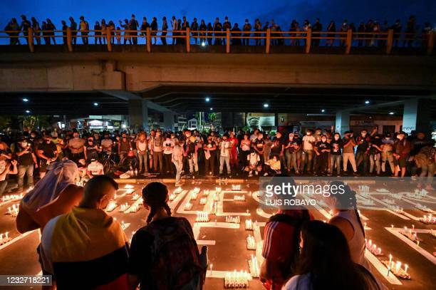 People gather around candles during a vigil on May 5, 2021 in Cali, Colombia, in honor of the demonstrators who died during protests against the...