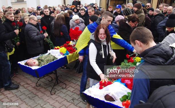 People gather around coffins with the bodies of Nikolay Troitsky and Aleksander Kutuzaky, two fighters of Ukrainian volonteers battalion of Azov who...