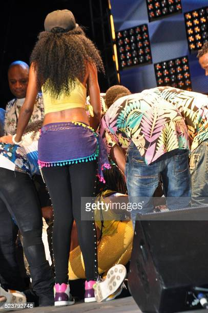 People gather around Congolese music star Papa Wemba after he collapsed on stage during the Femua music festival in Abidjan on April 24 2016 The...
