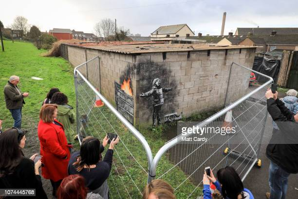 People gather around fences that have been erected to protect the latest piece of artwork by the underground guerrilla artist Banksy on December 20...