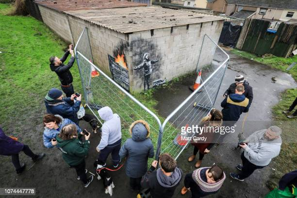 People gather around fences that have been erected to protect the latest piece of artwork by the underground guerrilla artist Banksy that has...