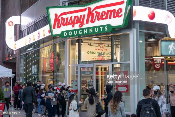 People gather around outside the newly opened Krispy Kreme store in Times Square as the city continues Phase 4 of re-opening following restrictions...