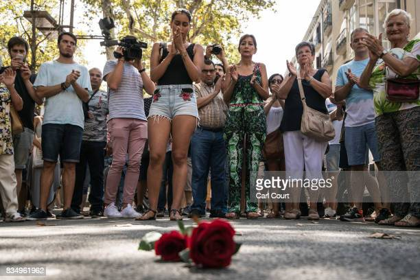 People gather around roses laid on the ground on Las Ramblas after a one minute's silence for the victims of yesterday's terrorist attack on August...