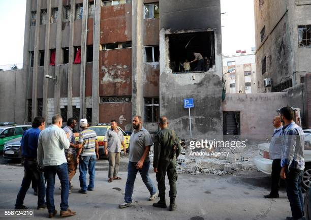 People gather around the blast site after a twin suicide bombing attack following a carbomb explosion on a police station in alMidan Neighborhood of...