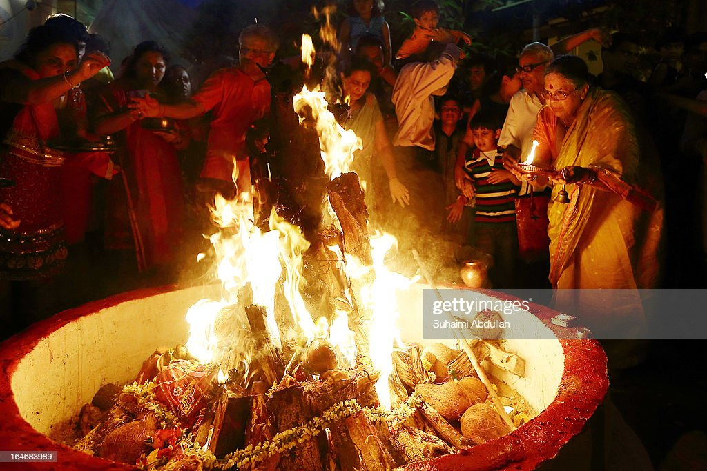 People gather around the bornfire to offer prayers as they celebrate Holika Dahan on March 26, 2013 in Singapore. Holika Dahan, or burning of demon Holika, is celebrated the night before the Holi festival and is said to commemorate the escape of Prahlad, adevotee of god Vishnu, from being burned when carried by Demoness Holika into a fire. The bonfire is said to epitomize the victory of good over evil.