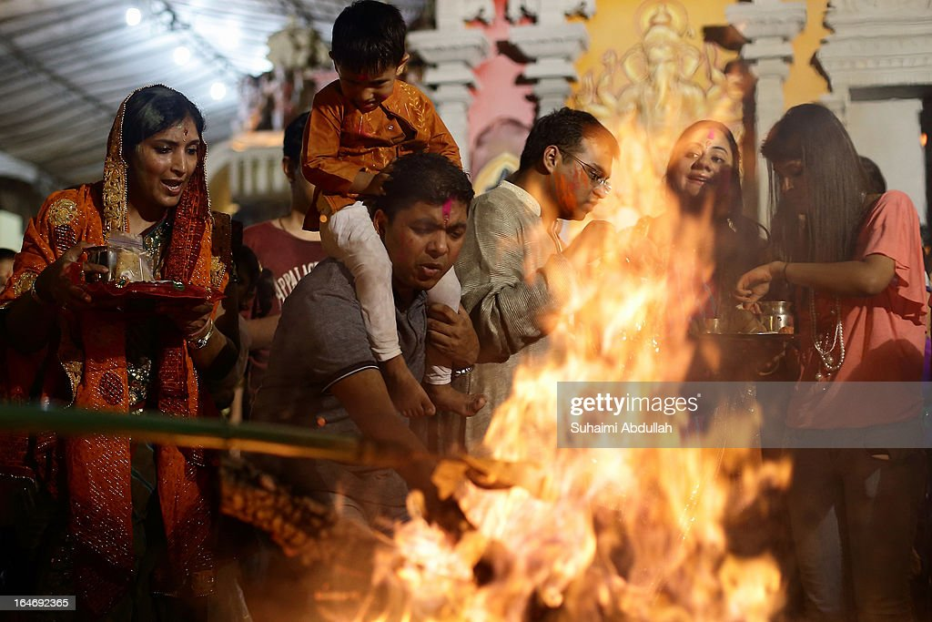 People gather around the bornfire to offer prayers as they celebrate Holika Dahan on March 26, 2013 in Singapore. Holika Dahan, or burning of demon Holika, is celebrated the night before the Holi festival and is said to commemorate the escape of Prahlad (devotee of god Vishnu) from being burned when carried by Demoness Holika into fire. The bonfire epitomizes the victory of good over evil.