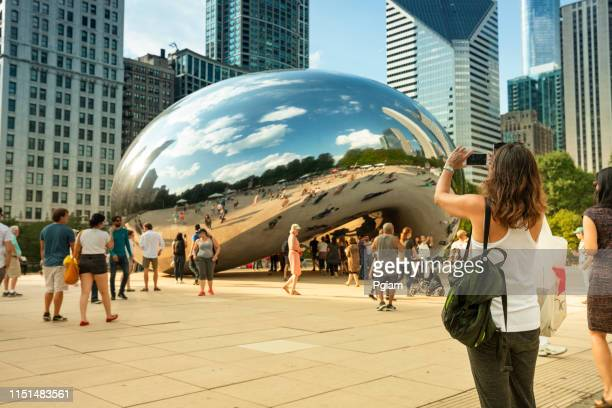 people gather around the cloud gate bean and chicago skyline in summer - millenium park stock photos and pictures