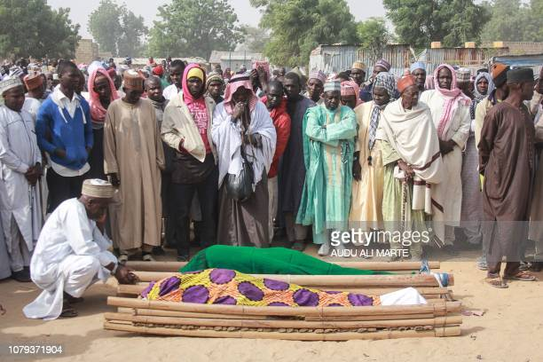 People gather around the corps of attack victims during their burial ceremony at the Sajeri village on the outskirts of the Borno state capital...
