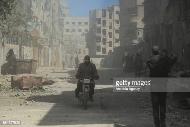 People gather around the damaged buildings after Assad Regime's airstrike over residential areas in Zamalka town of Eastern Ghouta Region of Damascus...