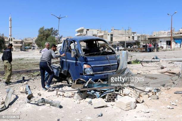 People gather around the damaged vehicles after the war crafts belonging to the Assad regime forces carried out airstrikes on the Khan Shaykhun town...