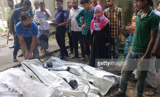 People gather around the dead bodies of workers after a fire broke out in a textile factory in Gazipur on July 3 2019 Fire tore through a textile...