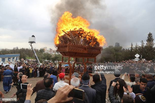 People gather around the fire during the Newroz celebrations the traditional Iranian festival of spring which starts at the exact moment of the...