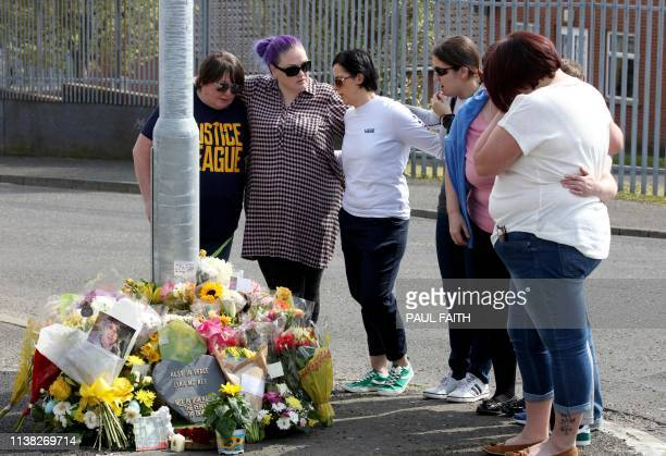People gather around the floral tributes placed at the scene in the Creggan area of Derry in Northern Ireland on April 20 2019 where journalist Lyra...