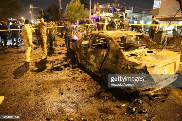 People gather around the incident site as security forces cordon the area after a roadside parked carbomb attack in Karrada district of Baghdad Iraq...