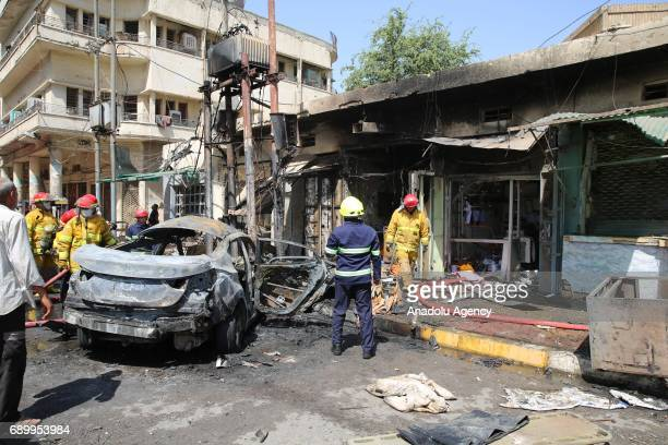 People gather around the incident site as security forces cordon the area after a roadside parked carbomb attack in Baghdad Iraq on May 30 2017