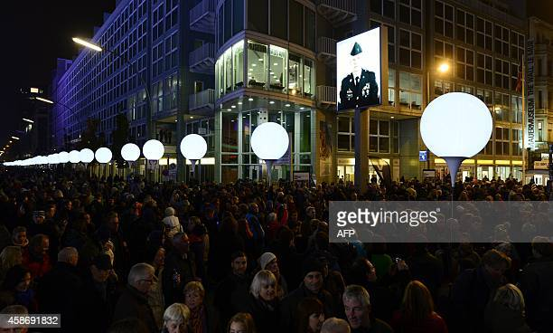People gather around the Light Border a lightened balloons installation on the route of the former border between East and WestBerlin to mark the...