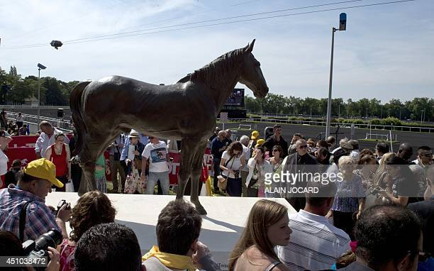 People gather around the newly unveiled bronze statue of French trotter Ourasi fourtime winner of the Prix d'Amerique at the Vincennes Racecourse in...