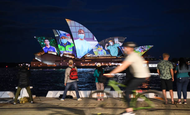 AUS: Sydney Opera House Sails Light Up In Tribute To Frontline Workers As NSW Reaches 80% Vaccine Milestone
