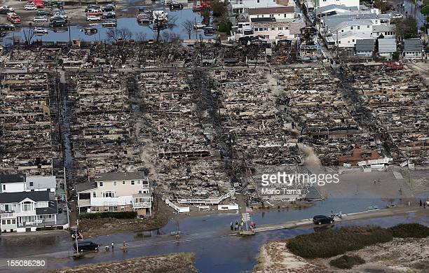 People gather around the remains of burned homes after Superstorm Sandy on October 31, 2012 in the Breezy Point neighborhood of the Queens borough of...