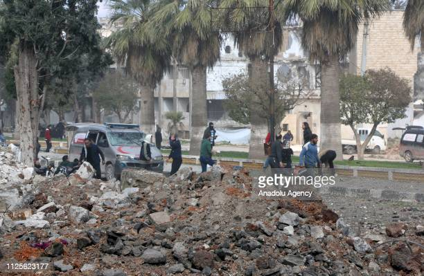 People gather around the wreckage at the site after the consecutive bomb attacks with two bombladen vehicles in Idlib city centre Syria on February...