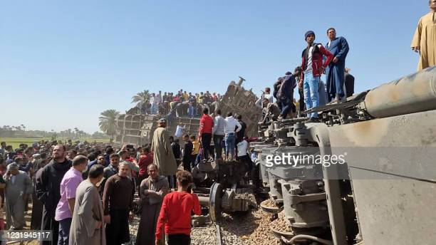 People gather around the wreckage of two trains that collided in the Tahta district of Sohag province, some 460 kms south of the Egyptian capital...