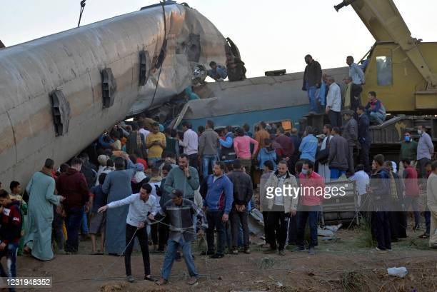 People gather around the wreckage of two trains that collided in the Tahta district of Sohag province, some 460 kilometres south of the Egyptian...