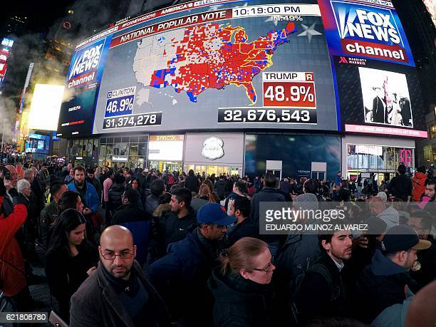 TOPSHOT People gather around Times Square to see the early results of the US presidential election on November 8 2016 in Manhattan New York / AFP /...
