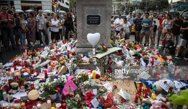 People gather around tributes laid on Las Ramblas near the scene of yesterday's terrorist attack on August 18 2017 in Barcelona Spain Fourteen people...