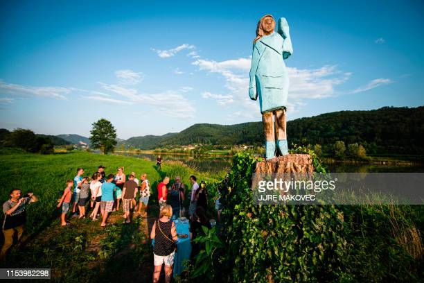 TOPSHOT People gather around what conceptual artist Ales 'Maxi' Zupevc claims is the first ever monument of Melania Trump set in the fields near the...