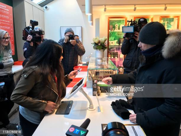 People gather as a customer buys CBD oil at the new Fire and Flower pot store on April 1 2019 in Ottawa Ontario The first bricks and mortar retail...
