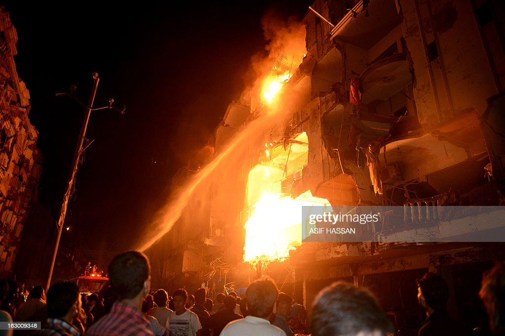 People gather as firefighters try to extinguish fire at the site of bomb blast in Karachi on March 3, 2013. A bomb attack in Pakistan's largest city Karachi on Sunday killed at least 23 people, including women and children, and wounded 50 others, police said.