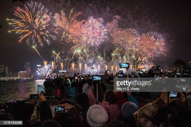 People gather as fireworks light up the city's skyline marking the New Year celebrations in Hong Kong on January 01 2019 in Hong Kong Hong Kong