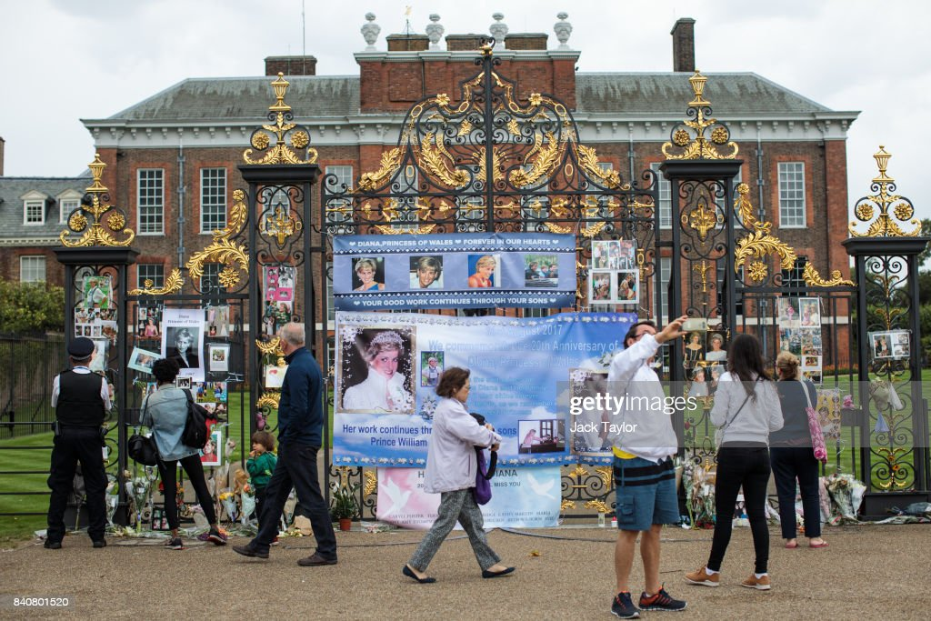 People gather as floral tributes, photographs and messages sit outside an entrance gate to Kensington Palace ahead of the 20th anniversary of the death of Diana, Princess of Wales on August 30, 2017 in London, England. On August 31, 1997 Princess Diana was fatally injured, aged 36, in a high speed car crash in a Paris, France. The months following her death saw a huge public outpouring of grief with a sea of tributes left by members of the public outside Kensington Palace.