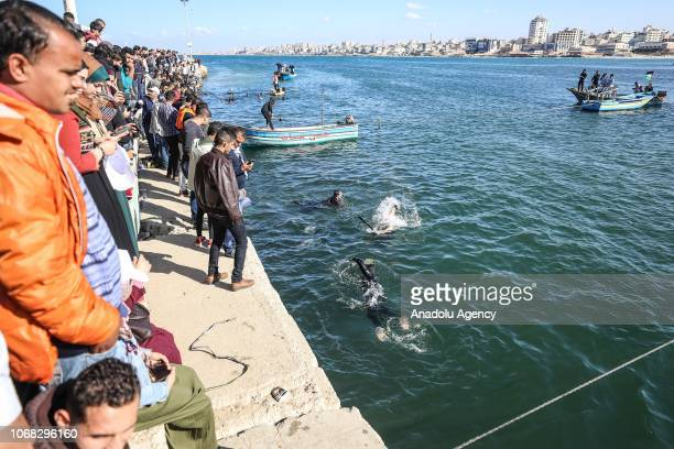 People gather as Palestinian volunteer divers clean up Port of Gaza from waste materials in Gaza City Gaza on December 4 2018
