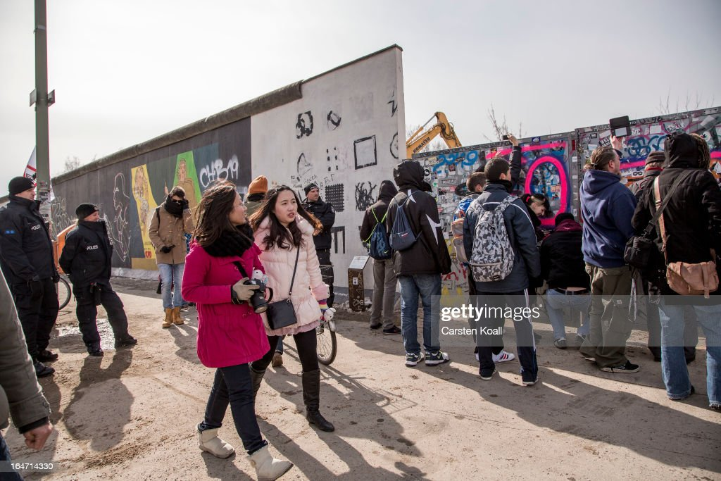 People gather as police stand guard next to a section of the Berlin Wall which has been removed to make way for a luxury apartments development on March 27, 2013 in Berlin, Germany. Activists are seeking to stop a stretch of the Berlin Wall, known as the East Side Gallery, from being developed on by a real estate development company. A previous attempt by the developer to remove approximately 25 meters of the wall sparked protests that led to minor clashes with police. Negotiations had been underway and city officials had even offered the developer an alternative property, though removal continued today unannounced and to the surprise of opponents. The East Side Gallery is over one kilometer long and is among the city's biggest tourist attractions.