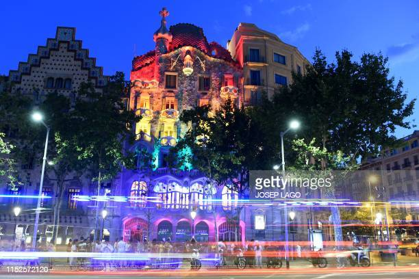 People gather as Spanish Catalan architect Antoni Gaudi's Casa Batllo is lit with the rainbow flag for Gay Pride month in Barcelona on June 28 2019
