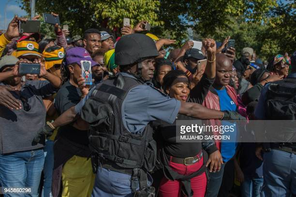 People gather as the casket carrying the anti-apartheid icon Winnie Madikizela-Mandela is returned to her home in Soweto, Johannesburg on April 13,...