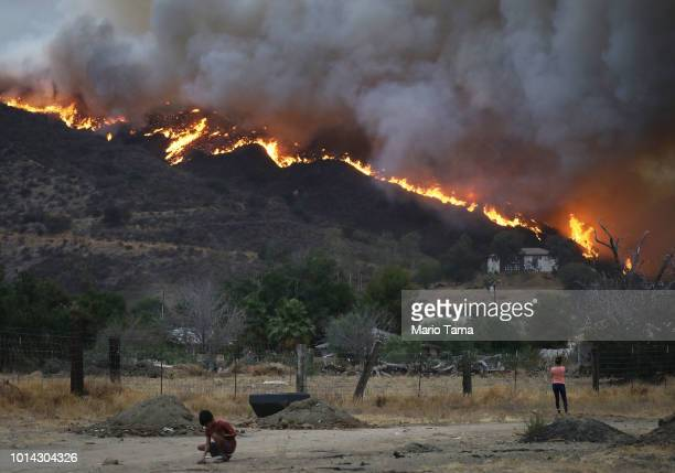 People gather as the Holy Fire burns near homes on August 9 2018 in Lake Elsinore California The fire continues to grow amidst a heat wave and has...